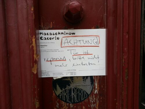 Zettel an einer Haustür in Dresden mit der Aufschrift: Tür wurde repariert, bitte nicht mehr eintreten.