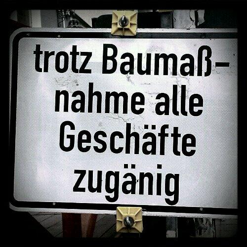 Schild mit Aufschrift: Trotz Baumaßnahme alle Geschäfte zugänig